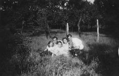Eine gruppe von jugendlichen sitzt mit einem hund im august 1948 auf