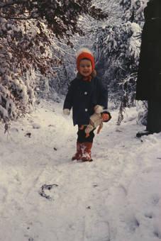 Kind mit Puppe im Schnee
