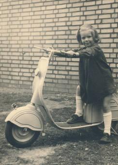 Mädchen sitzt auf Roller