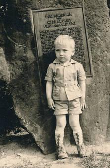 Junge lehnt an Gedenkstein