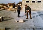 Drei Arbeiter auf einem Dach