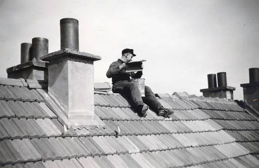 Mann sitzt auf einem Dach
