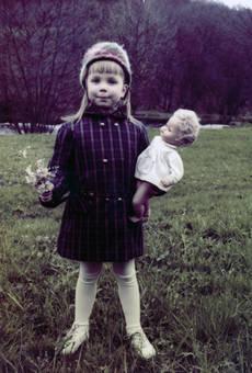 Kind mit Blumen und Puppe