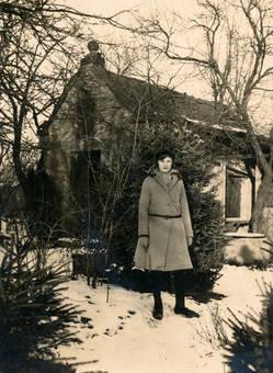 Frau vor Haus im Schnee