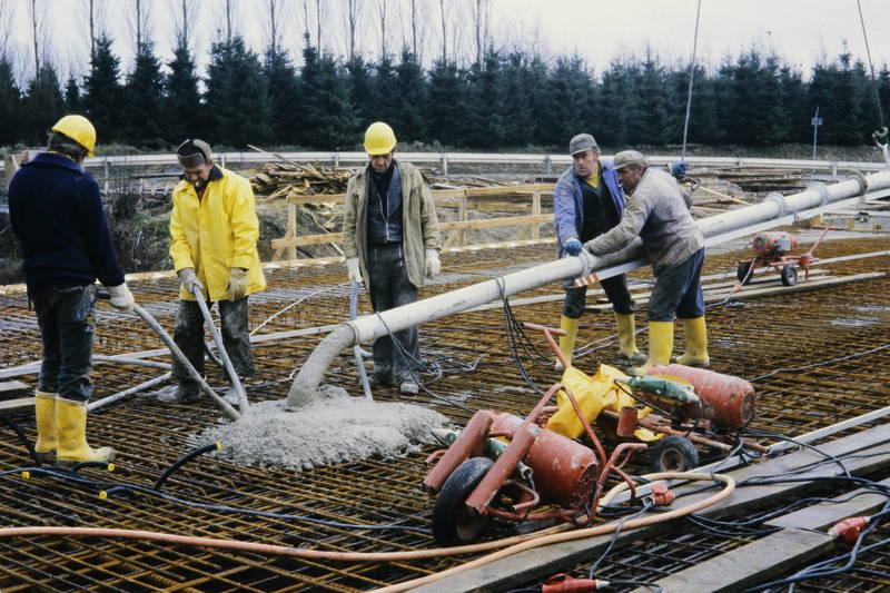 Bauarbeiter, Baustelle, Beton, Betoneinbau, Flaschenrüttler, Gummistiefel, Regenjacke