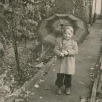 Mit Regenschirm im Garten