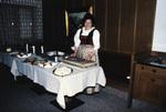 Frau steht vor einem Tisch