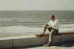 Mann sitzt am Strand