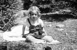 Kind sitzt auf einer Wiese