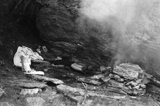 Liegende Frau vor einem Felsen