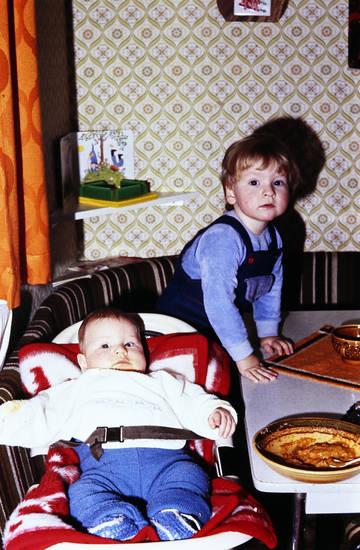 Bolognese, Eckbank, essen, füttern, Geschwister, kind, Kindheit, Latzhose, Sitzkorb, tapete