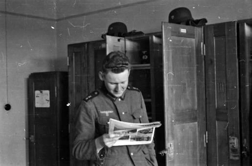 Soldat vor Regal liest Zeitung