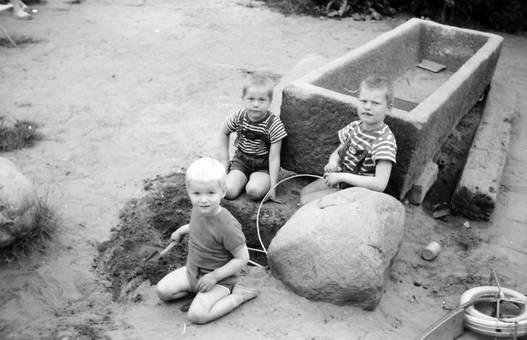 Kinder sitzen um ein Loch