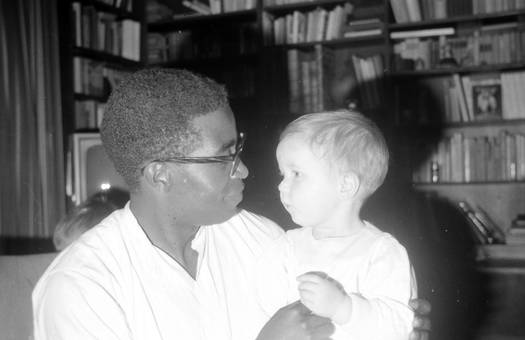 Mann mit Kind vor Bücherregal