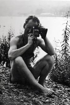 Mann mit Kamera am See