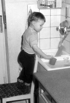 Kind vor der Spüle