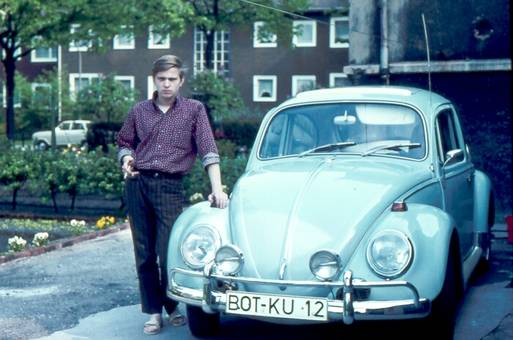 Junger Mann mit VW Käfer